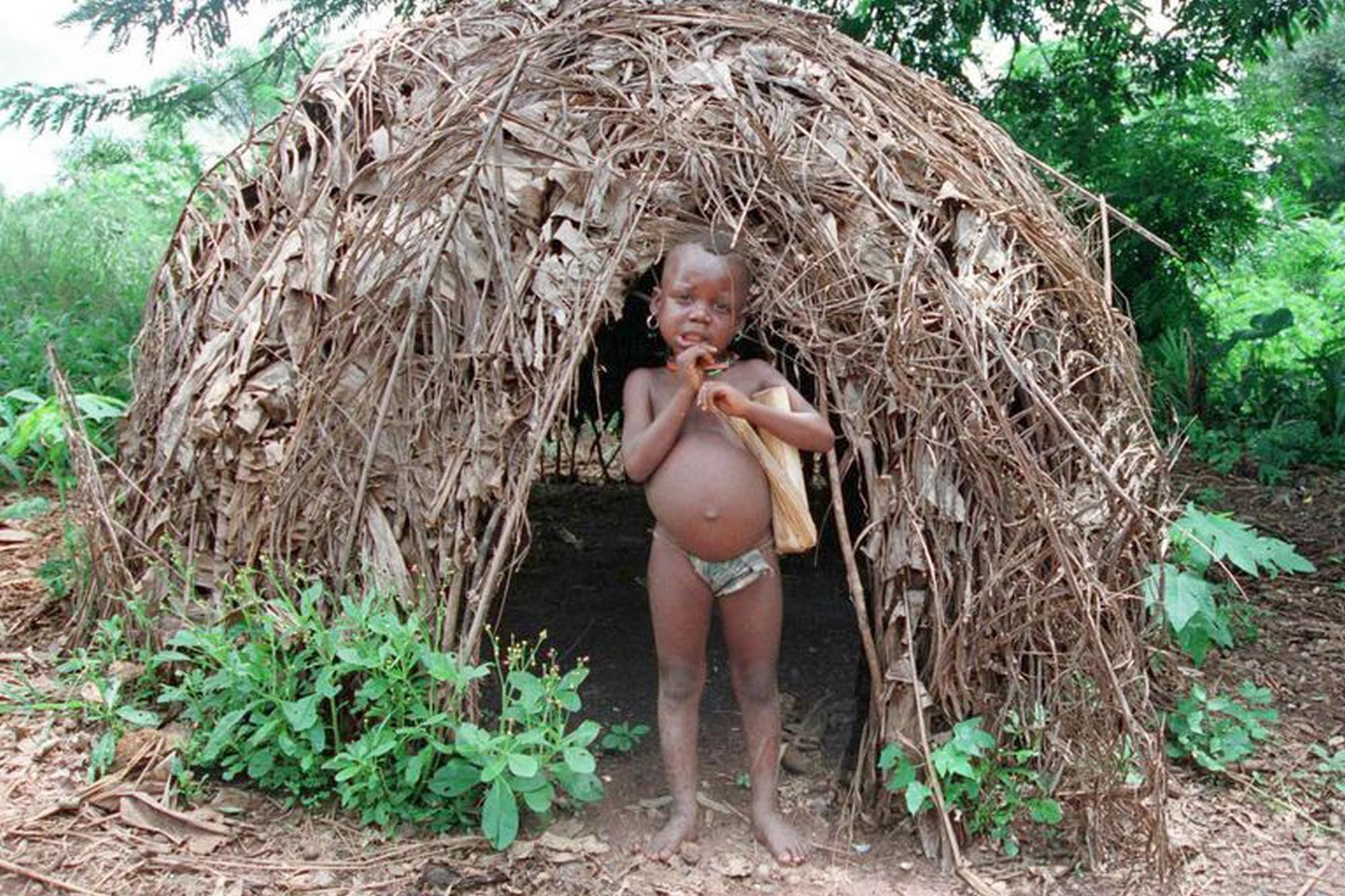 Юный пигмей у хижины из прутьев и листьев. Габон, Центральная Африка (Desirey Minkoh / AFP).