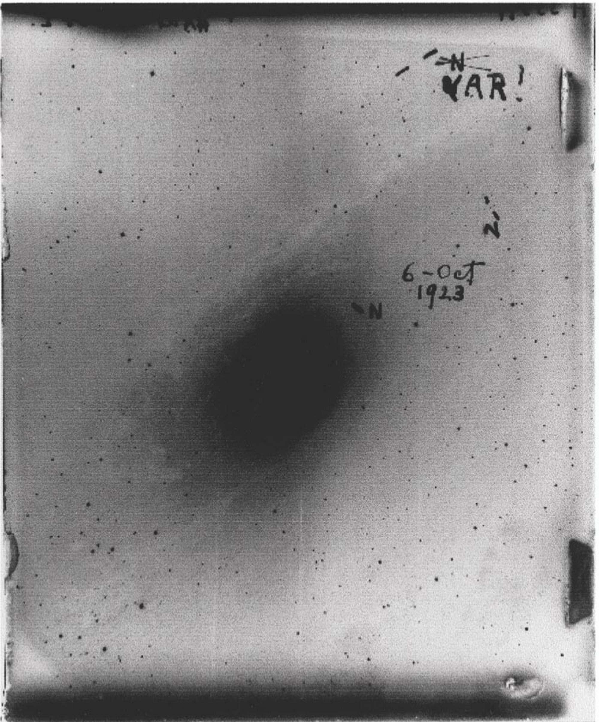 Галактика Туманность Андромеды на фотопластинке Эдвина Хаббла. Хаббл обнаружил, что звезда, первоначально помеченная им как новая (N), на самом деле является переменной (VAR), похожей на хорошо изученные переменные звёзды в нашей Галактике. Хаббл подсчитал расстояние до этой звезды и обнаружил, что она была гораздо дальше, чем все известные звёзды. Из этого следовало, что «туманность» Андромеды является отдельной галактикой (Pearson Education / Addison-Wesley).